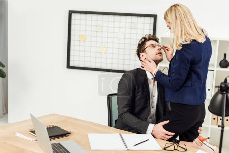 Photo for Attractive young businesswoman flirting with business colleague at workplace in office - Royalty Free Image