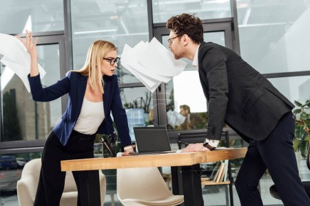 passionate businesswoman throwing papers away while looking at businessman at workplace, office romance concept