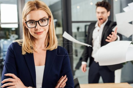 selective focus of smiling businesswoman in eyeglasses and angry screaming boss throwing papers behind in office