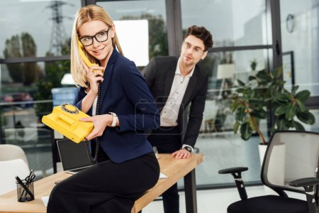young businessman looking at beautiful businesswoman with yellow retro telephone in office