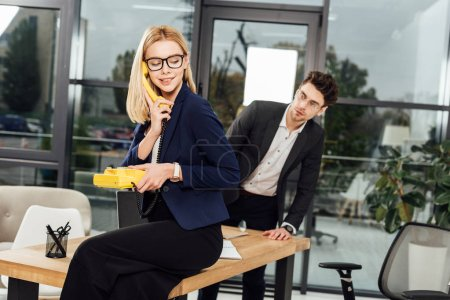 businessman looking at young businesswoman with yellow retro telephone at worklace in office