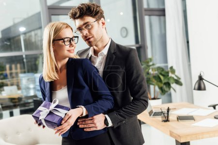 businessman hugging young colleague with gift in office, office romance concept