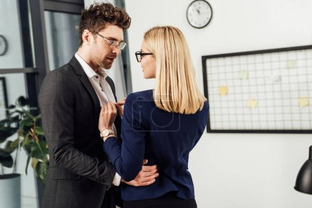 young businesswoman undressing colleague in office, flirting and office romance concept