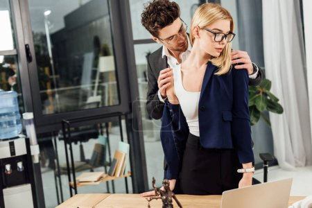 businessman undressing businesswoman at workplace in office