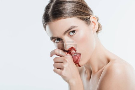 naked woman with injury on face licking blood from hand isolated on white