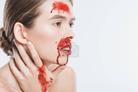 close up of nude female domestic violence victim with red blood isolated on white