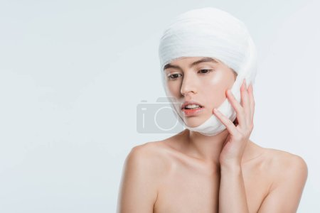nude woman with bandages on head after plastic surgery isolated on white