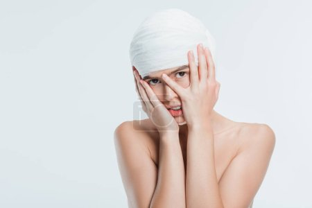 naked woman with white bandages and hands on face isolated on white