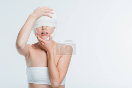 woman with bandages touching head after plastic surgery isolated on white