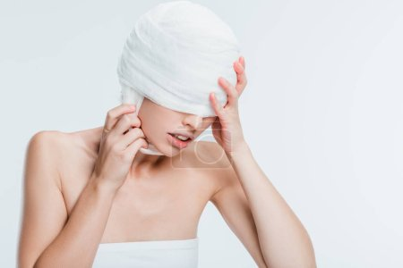 woman with bandages touching head isolated on white