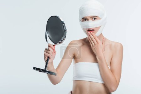 frightened woman with bandages holding mirror isolated on white
