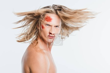 adult man with bloody bruises on face waving hair isolated on white