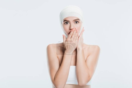 scared woman with bandages over head after plastic surgery isolated on white