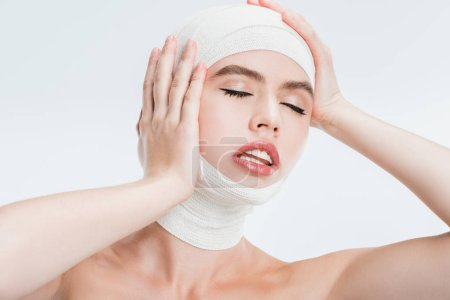 close up of adult beautiful woman after plastic surgery touching head isolated on white