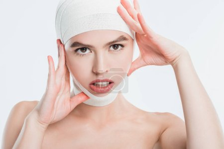 close up of woman with bandages over head after plastic surgery isolated on white