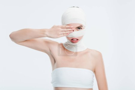 woman with bandages after plastic surgery hiding eye behind hand isolated on white