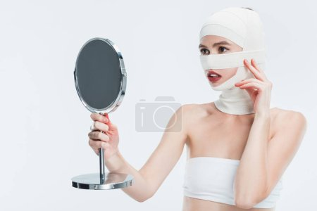 woman with bandages over head looking at mirror isolated on white
