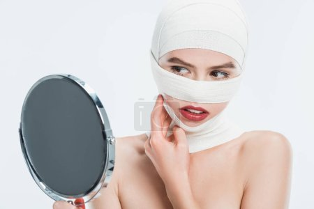 close up of woman with bandages over head looking at mirror isolated on white