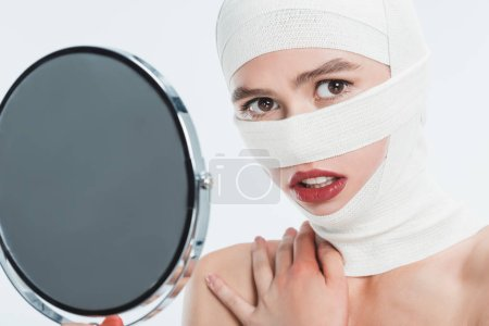 close up of woman with bandages over head holding mirror and looking at camera isolated on white