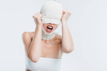 angry woman with bandages on head screaming after plastic surgery isolated on white