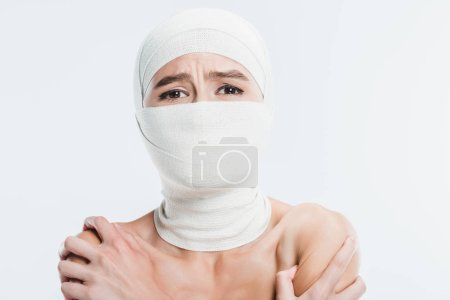 close up of naked painful woman with white bandages over face and head isolated on white