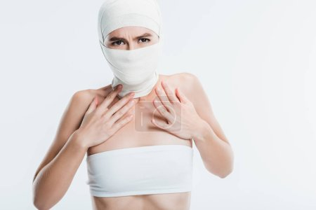 scared woman with white bandages over face and head isolated on white