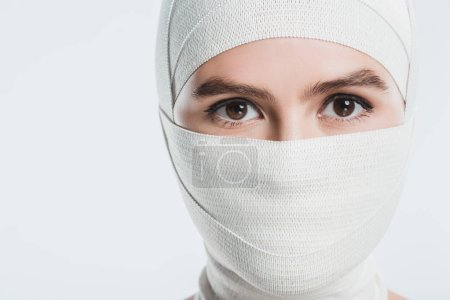 woman with white bandages over face and head looking at camera isolated on white