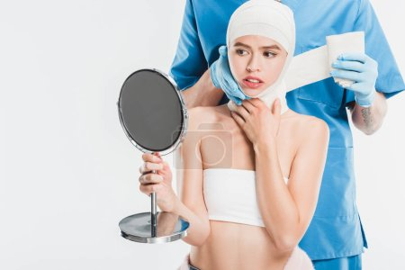 surgeon in gloves taping up face with bandage after plastic surgery while woman looking at mirror isolated on white