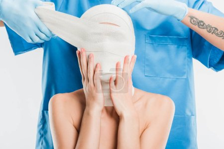 close up of plastic surgeon in gloves taping up woman face with bandage isolated on white