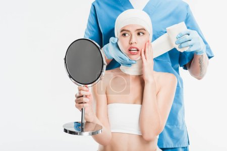 surgeon in gloves taping up face with bandage after plastic surgery while scared woman looking at mirror isolated on white
