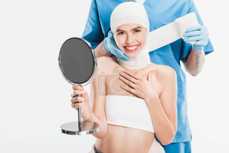surgeon in gloves taping up face with bandage after plastic surgery while smiling woman holding mirror isolated on white
