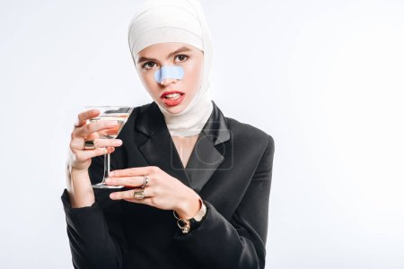 stylish woman with bandages over head after plastic surgery holding glass with cocktail isolated on white