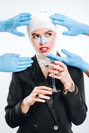 hands in gloves touching woman with bandages after plastic surgery and cocktail isolated on white
