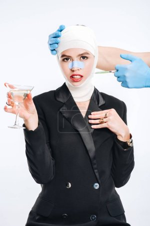 hands in gloves holding syringe while woman posing with cocktail isolated on white