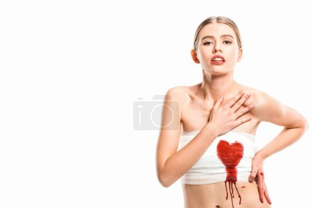 adult woman in bandages with bloody heart isolated on white