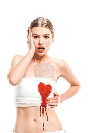 adult scared woman in bandages with bloody heart isolated on white