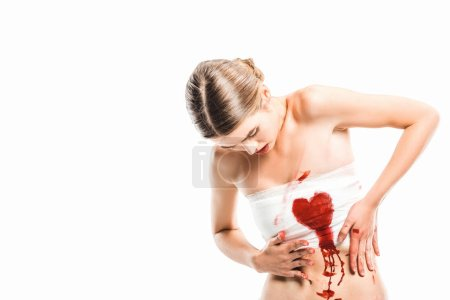 adult woman in bandages looking at bloody heart isolated on white