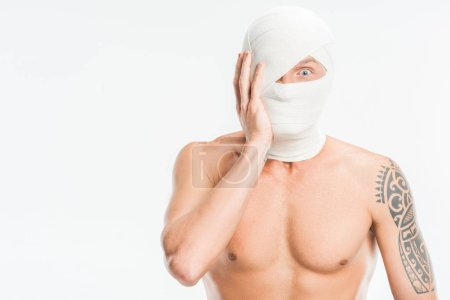 scared nude man with bandages over head after plastic surgery isolated on white