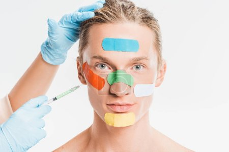 doctor doing injection to man with multicolored patches on face isolated on white