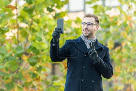 Photo pour Gai homme prenant selfie et montrer signe de paix - image libre de droit
