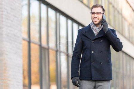 cheerful man talking on smartphone near building