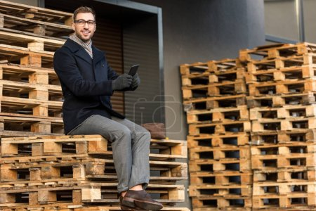 handsome smiling man using smartphone and sitting on wooden pallets