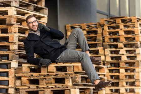 handsome smiling man talking on smartphone and laying on wooden pallets