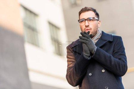 Photo pour Bel homme réchauffant les mains avec bâtiment flou - image libre de droit