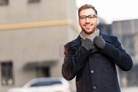 handsome smiling man holding coat collar at parking