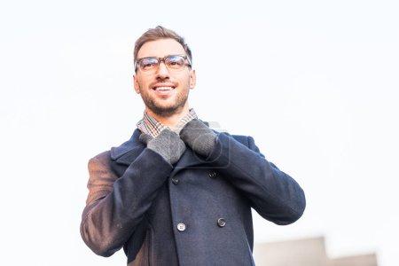 handsome cheerful man holding coat collar