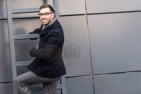 cheerful handsome man climbing on ladder near building