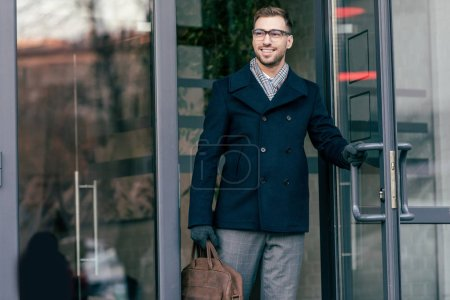 adult smiling handsome man in glasses with bag leaving building