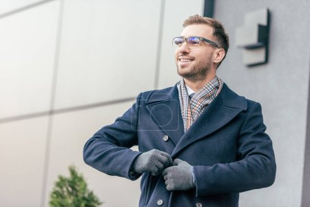 adult smiling handsome man in glasses fastening coat near building