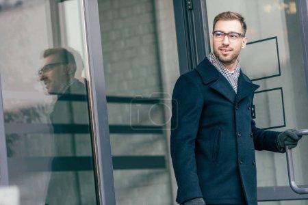 adult handsome man in glasses leaving building